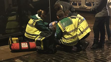 Norwich SOS Bus staff look after a woman on the floor outside of a bar
