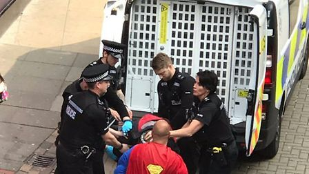 A man dressed as Superman watched as police arrested a man near Castle Mall in Norwich. Picture: Pet