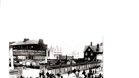 A parade with band marches past the Yarmouth Beach Station goods and coal depot in Euston Road early