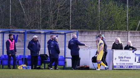 Lowestoft Town captain Travis Cole leaves the pitch at Stratford Town with physio Adam Woodrow havi