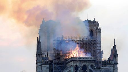 A firefighter tackles the blaze as flames and smoke rise from Notre Dame cathedral as it burns in Pa