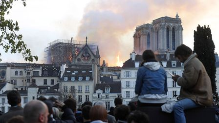 People watch as flames and smoke rise from Notre Dame cathedral as it burns in Paris, Monday, April