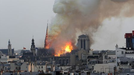 Flames rise from Notre Dame cathedral as it burns in Paris, Monday, April 15, 2019. Massive plumes o