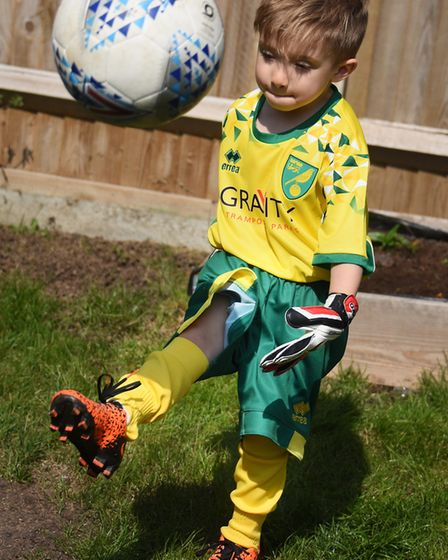 Football mad four-year-old Norwich City super fan Oscar Drewery playing in the garden at his home in