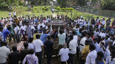 Sri Lankans prepare to burycoffins carrying remains two people who were killed in the Easter Sunday