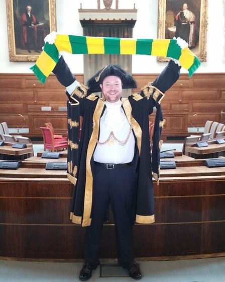 Lord mayor Martin Schmierer holds a Norwich City scarf aloft in the council chamber. Picture: Courte