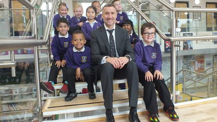 Stuart Allen, headteacher at Mile Cross Primary School, with year one and two pupils. The school was