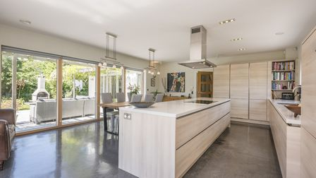 The spacious kitchen offers a large central island and separate dining area with patio doors which l