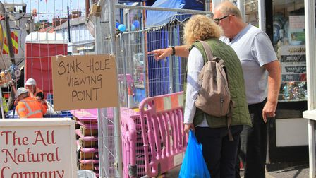 Workers have put up a 'sinkhole viewing point' sign, allowing passers-by to watch as repair work is