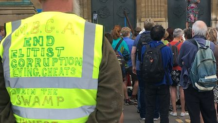"""A man wearing a high-vis jacket emblazoned with one of Donald Trump's favourite sayings, """"drain the"""