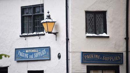 Snow on lamps and window sills as Elm Hill is transformed into a Victorian style winter setting for