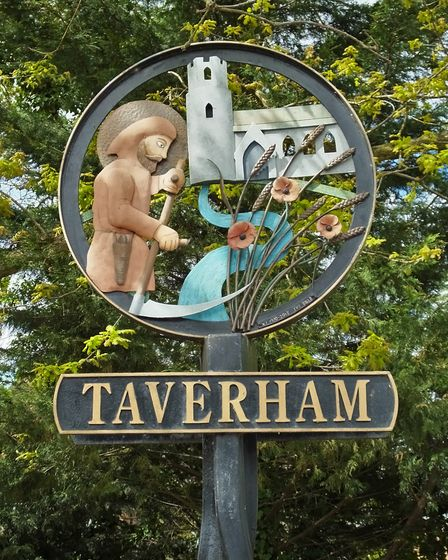 The Taverham village sign, depicts St Walstan holding a scythe in one hand and a cross in the other.