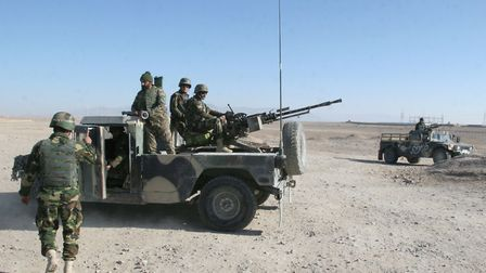 Afghan National Army soldiers guard at a checkpoint on the way to the Sangin district of Helmand pro