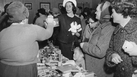 Earsham Church sale, lady buying items at the bric a brac table. sorry no date? c12035 pic to
