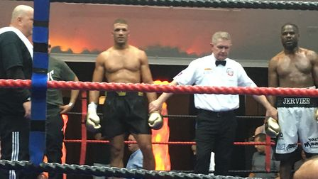 Iain Martell is about to have his arm raised in victory by referee Lee Cook after beating Ossie Gerv