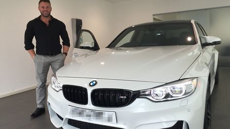Scott Wolfe, who was jailed for an online nutrition scam, posing with one of the cars bought during
