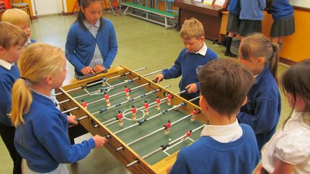 To celebrate the Women's World Cup, children from Fairhaven Primary School are holding a table footb