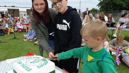 Two of the oldest pupils in the school cutting one of the many celebration cakes with the youngest p