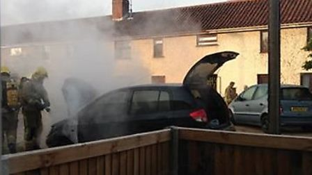 Firefighters working to extinguish a car targeted by arsonists on Appleyard Crescent. Photo: Submitt