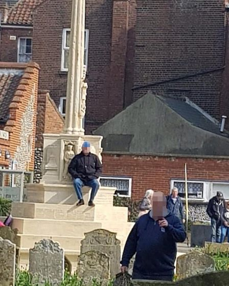 A man was photographed seated on the towns war memorial during the Cromer Vintage 1960s Festival on