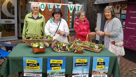 Holt WI member Dawn Rose, president Rita Gee and Gillian Pilgram handing out a posie of flowers to t