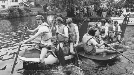 This group of rowers is trying to steer a 'shark' raft downriver past Pull's Ferry in Norwich, June
