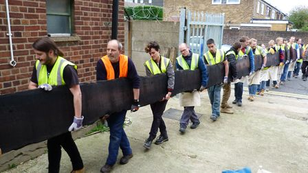 Part of the Fenland Black Oak being carried into the college where it will be transformed into a tab