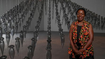 Magdalene Odundo stands with her installation Transition II as part of The Journey of Things exhibit