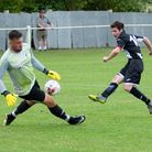 Swaffham's Alex Vincent is denied by the Godmanchester keeper, who gets just enough on the ball to d