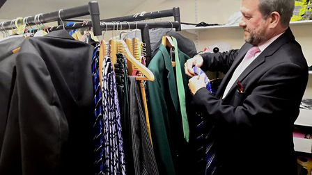 Marc Hall, who trains funeral directors at Rosedale, sorts the various suits available for funerals.