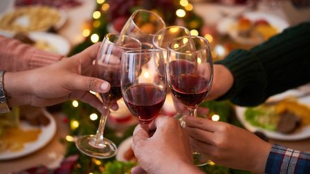 Friends toasting Christmas lunch with a glass of light red wine. Picture: Getty Images/iStockphoto