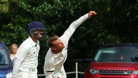 Skipper Ashley Watson turns his arm over, with former Norfolk colleague Garry Park in close attendan