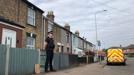 A police officer stands outside a house on Victoria Road in Lowestoft after a woman was found with a
