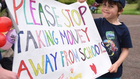 Max Hernandez Brandon, five, with the sign he designed for the march against government 'under-fundi