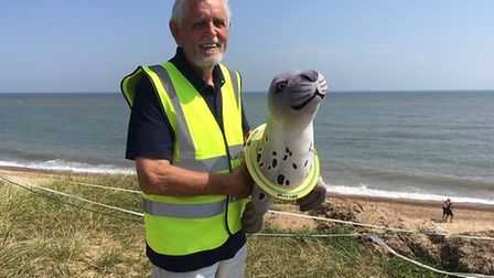 Chairman of the Friends of Horsey Seals with a cuddly seal at the launch of a campaign raising aware