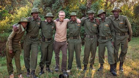 Photographer and film maker Chris Taylor pictured with the Maasai Mara rangers he worked with on a t