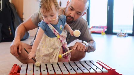 Lola Morris, 23-months-old, with her dad, Ronnie, in the music room at The Nook hospice, during the