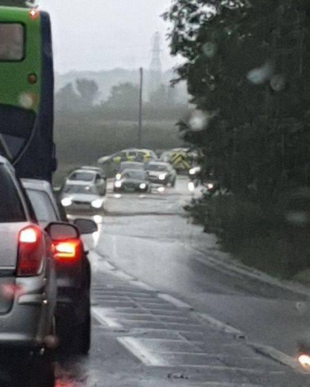 Police letting cars through the flood on the A47 past the Honingham roundabout. Picture: Nia Howe