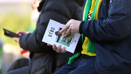 A fan reads the match programme before the Premier League match at Carrow Road, Norwich. PA Photo. P