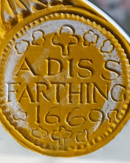 A coin with the words 'A Diss farthing 1669' on the Diss town sign. This represents a trader's token