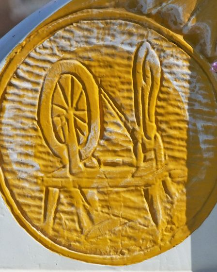 This panel on the Diss town sign showing a spinning wheel represents the historical importance of te