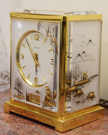 A rare gold plated Atmos clock, with white Lucite panels decorated with gold chinoiserie scenes, sel