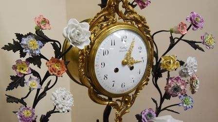 A French porcelain mantel clock with patinated branches and finely worked flowers, dated around 1870