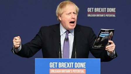 Prime Minister Boris Johnson holds up his party's manifesto during its launch at Telford Internation