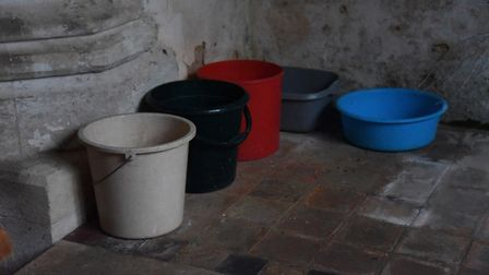 Buckets and bowls to catch the rainwater running through the leaking roof at Wolferton Church. Pictu