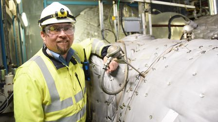 Adam Kennard, King's Lynn Power Station manager, with the high pressure steam turbine. Picture: DENI