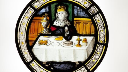 This stained glass roundel made in Norwich 500 years ago and showing a king at a festive feast is ou