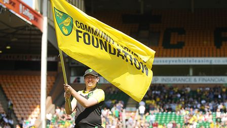A young man waves the Community Sports Foundation flag at Carrow Road Picture: Ian Burt