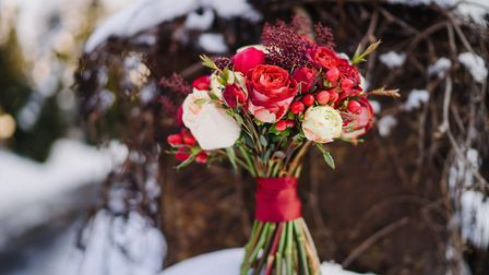 wedding bouquet of red and white flowers on snow outdoors in winter