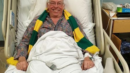 Tony Kirwan smiling and wearing his Norwich City scarf just hours after suffering a cardiac arrest a
